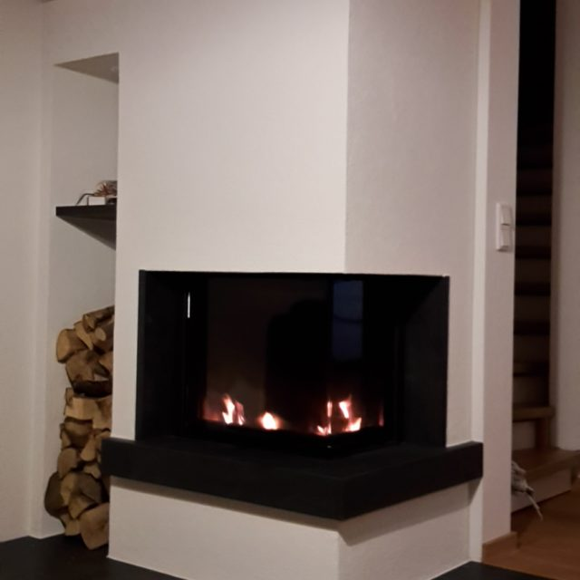 moderner Kamin mit einem schwarzen Marmor und Feuerschutz, integriertes Regal für Holz von Somnium Kamin