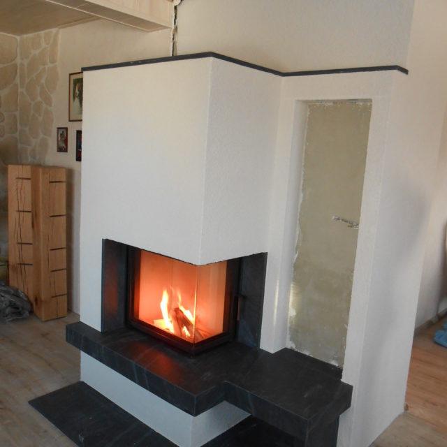 moderner Kamin mit einem schwarzen Marmorsims und extra Sitzfläche von Somnium Kamin