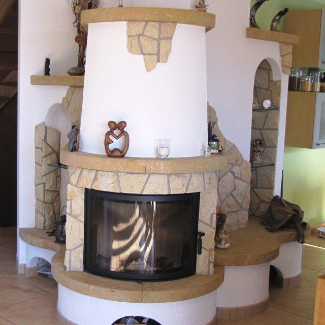 rustikaler, halbrunder Kamin mit Natursteinen von Somnium Kamin