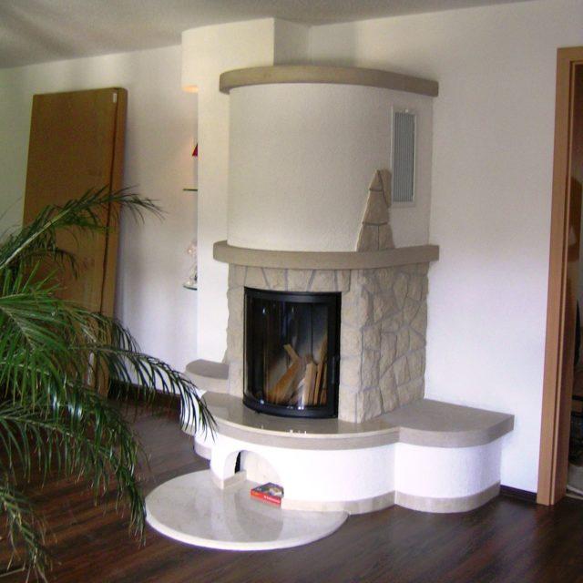 Kamin mit Natursteinen, Mamorsims und Feuerschutz von Somnium Kamin