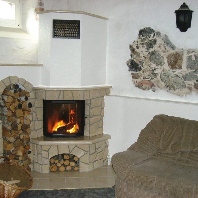 rustikaler Eckkamin mit Natursteinen und Feuerschutz von Somnium Kamin