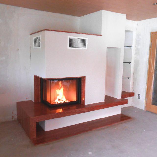 moderner Kamin mit einem roten Marmorsims und extra Sitzfläche und integrierten Regalen von Somnium Kamin